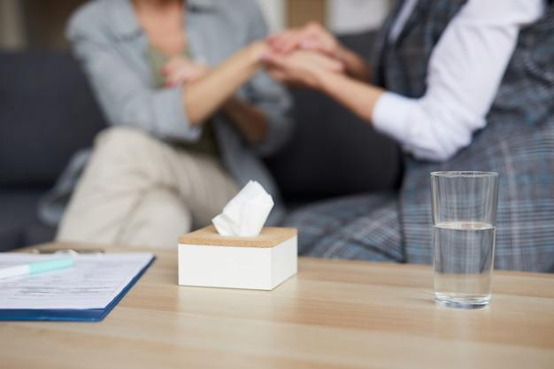 Zorgzame psycholoog hand in hand van vrouwelijke patiënt
