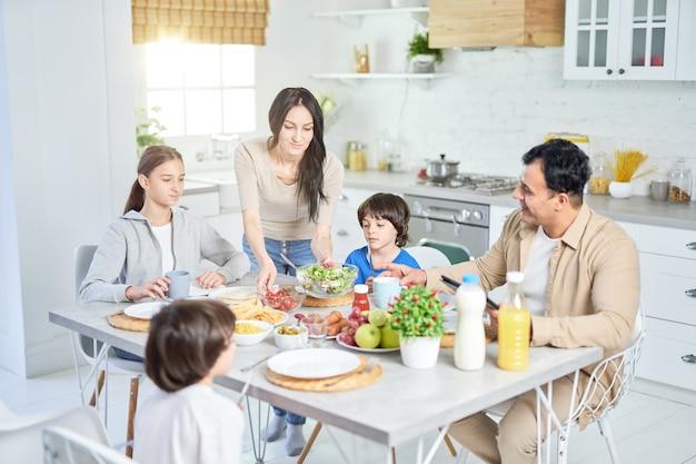 Zorgzame spaanse vrouw die salade serveert voor haar man en kinderen, staande in de keuken. latijnse familie die thuis samen dineert. selectieve focus
