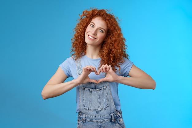 Zorgzame tedere mooie roodharige vriendin betuig sympathie tederheid zachte sympathie tilt hoofd glimlachend breed toon hart liefde gebaar borst koester hartstochtelijke romantische gevoelens, blauwe achtergrond.