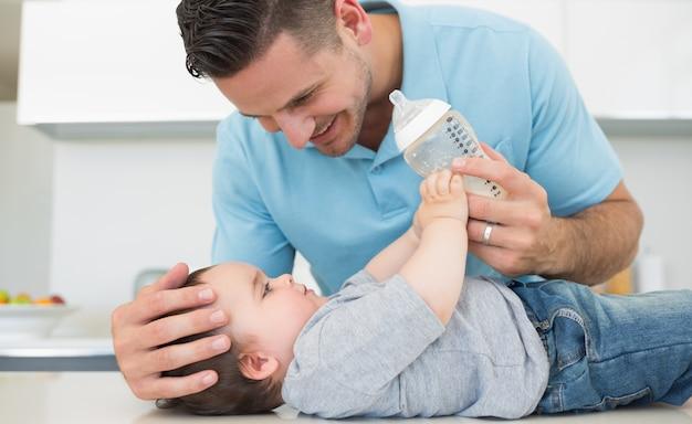 Zorgzame vader die melk voedt met baby