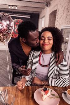 Zorgzame vriend. aardige positieve man die zijn vriendin kuste terwijl hij haar feliciteerde met haar verjaardag