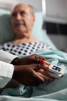 Zorgzame vriendelijke jonge arts-therapeut die de hand van de zieke oudere patiënt vasthoudt, troostend, medeleven toont, over de behandeling praat, terwijl hij ademt met behulp van een zuurstofmasker