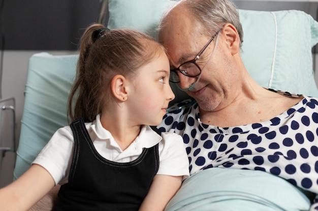 Zorgzame vrolijke kleindochter die voorhoofd aanraakt met zieke bejaarde grootvader