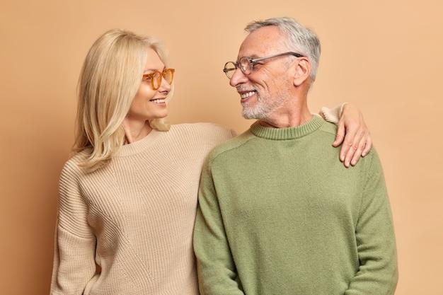 Zorgzame vrouw van middelbare leeftijd omarmt haar man kijkt met liefde en een brede glimlach