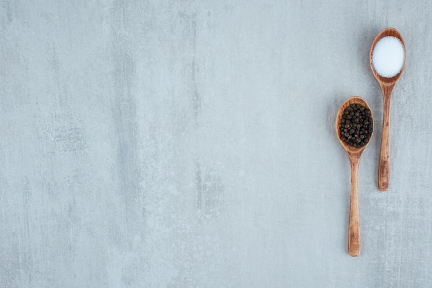 Zout en peperkorrels op houten lepels.