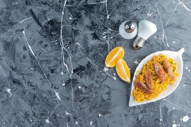 Zout, gesneden citroen naast vlees en noedels op een schaal, op de marmeren achtergrond.