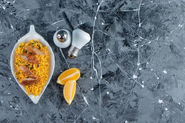 Zout, gesneden citroen naast vlees en noedels op een schotel, op de marmeren achtergrond.