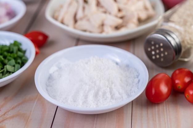 Zout in een witte lepel, tomaten op een houten tafel.