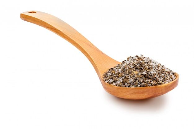 Zout met fijne kruiden (rozemarijn, oregano en zwarte peper) in een houten lepel.