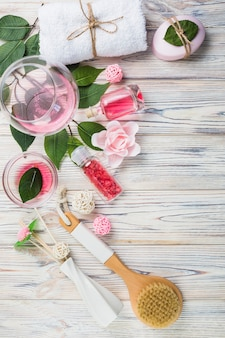 Zout; olie; handdoek; zeep; verlaat; bloemen en penseel op houten plank