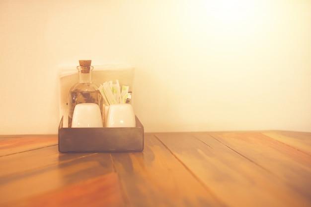 Zout pepersauzen azijn tandenstokers servetten op de vintage houten tafel in een café