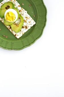 Zoute crackers met avocado met ei van bovenaf