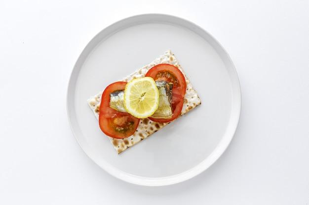 Zoute crackers met van bovenaf sardine, tomaat en citroen