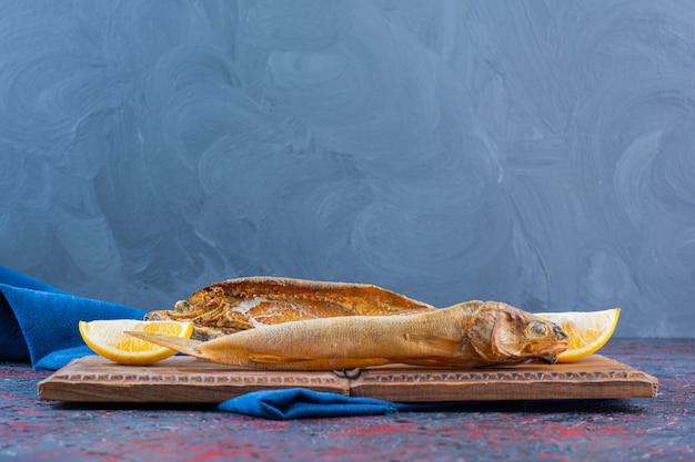 Zoute gedroogde vis geïsoleerd op een houten bord. Premium Foto