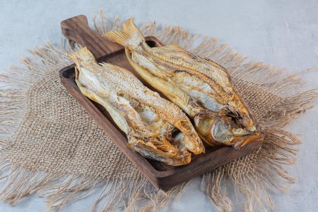 Zoute gedroogde vis geïsoleerd op een houten bord.