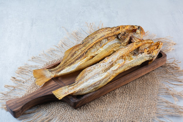 Zoute gedroogde vis geïsoleerd op een houten bord