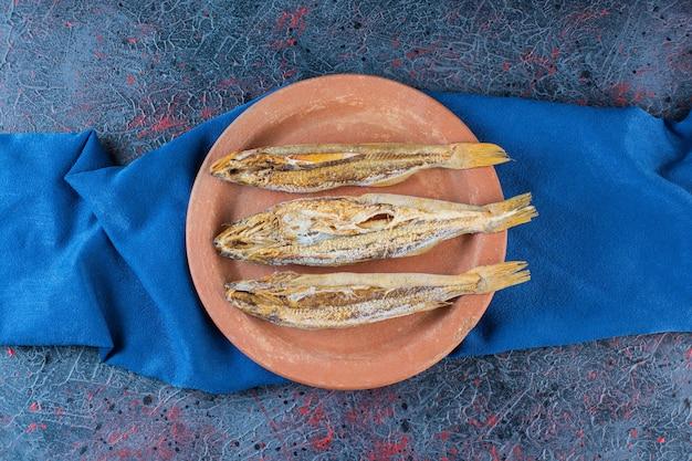 Zoute gedroogde vis geïsoleerd op een kleiplaat op een donkere achtergrond.