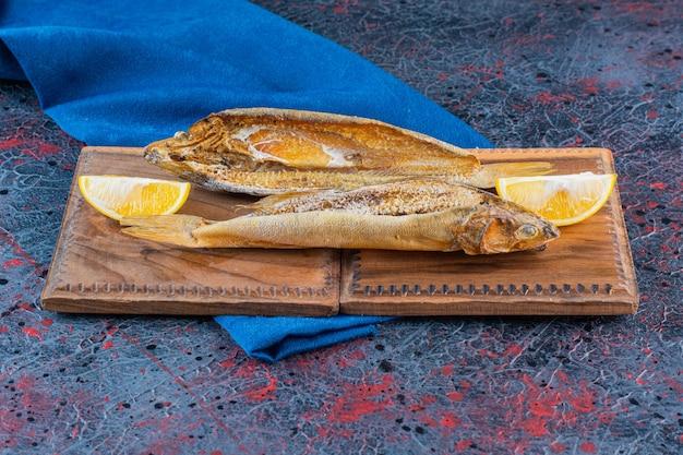 Zoute gedroogde vis met een schijfje citroen geïsoleerd op een houten bord