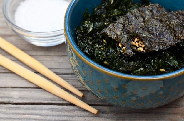 Zoute geroosterde gedroogde zeewier nori met sesamzaadjes in een blauwe kom op oude houten tafel