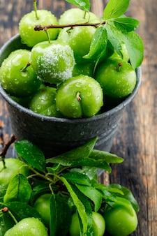 Zoute groene pruimen in een mini-emmer met bladeren hoge hoek uitzicht op een houten muur