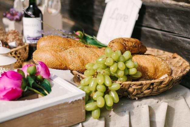 Zoute reep. viering. kaas bar. kaasreep van verschillende soorten kaas, druiven, olijven en brood versierd op vintage houten tafel met gebogen metalen poten, tafel staande op een groen gazon