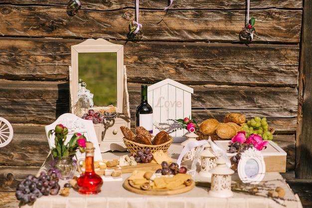 Zoute reep. viering. kaasreep van verschillende soorten kaas, druiven, olijven en brood versierd op vintage houten tafel met gebogen metalen poten, tafel staande op een groen gazon