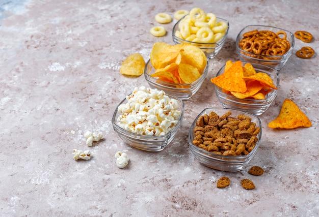 Zoute snacks. pretzels, chips, crackers, popcorn in kommen. ongezonde producten. voedsel slecht voor figuur, huid, hart en tanden. assortiment van snelle koolhydraten