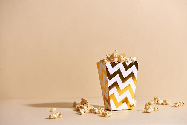 Zoute verse knapperige zelfgemaakte popcorn in gouden papieren beker in het mode-oppervlak
