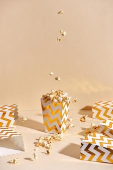 Zoute verse knapperige zelfgemaakte popcorn in gouden papieren beker in het modieuze beige oppervlak