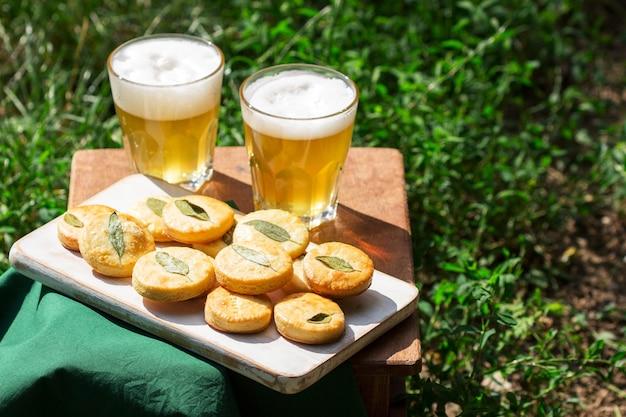 Zoute zandkoekkoekjes met salie en bier op een houten kruk.