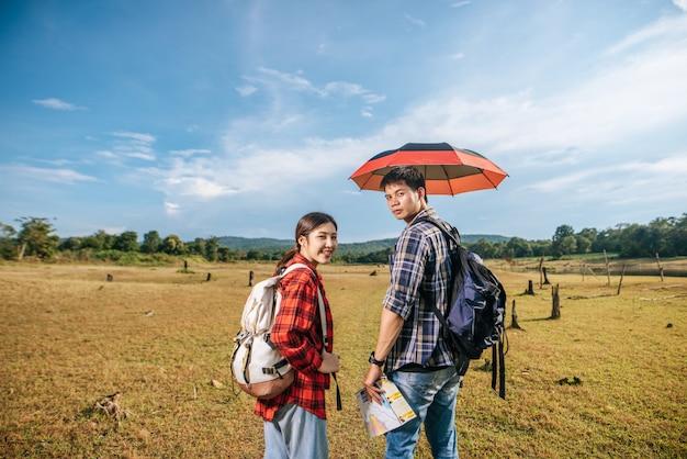 Zowel mannelijke als vrouwelijke toeristen dragen een rugzak die op het gazon staat.