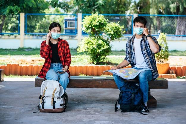 Zowel mannelijke als vrouwelijke toeristen zitten en kijken naar de kaart naast de spoorlijn.