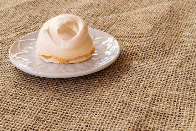 Zucht of zelfgemaakte meringue is een snoepje gemaakt van eiwit, suiker en citroen op het witte bord en een jute handdoek.