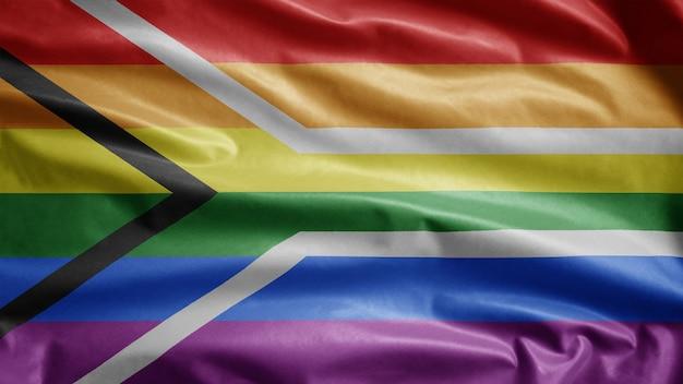 Zuid-afrika gay pride-vlag zwaaien op wind. zuid-afrikaanse lgbt-gemeenschap banner waait gladde zijde. doek stof textuur vlag achtergrond