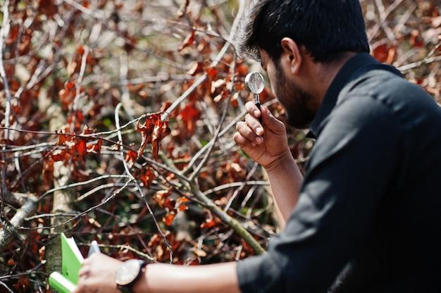 Zuid-aziatische agronoom landbouwer met klembord inspecteren gesneden bomen in de boerderij tuin. landbouw productieconcept.