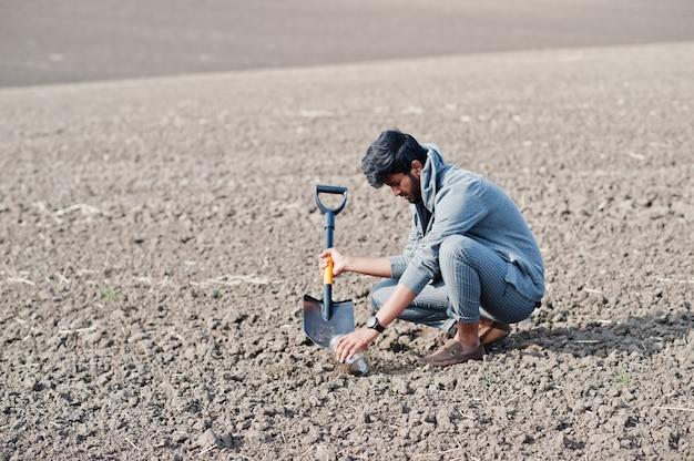 Zuid-aziatische agronoom landbouwer met schop inspecteren zwarte grond. landbouw productieconcept.