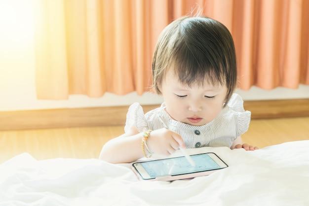 Zuigeling, baby op een wit bed, spelen of leren tekenen