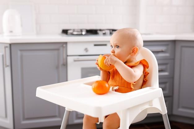 Zuigelingsmeisje die in hoge kinderstoel fruit op wit zitten