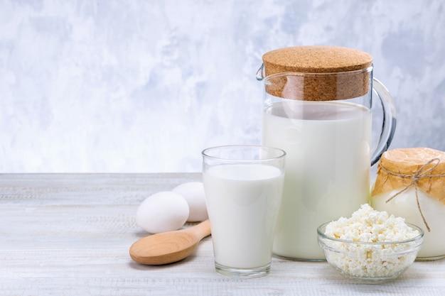 Zuivelproducten, melk, cottage cheese, eieren en zure room op houten tafel tegen grijze muur met kopie ruimte.