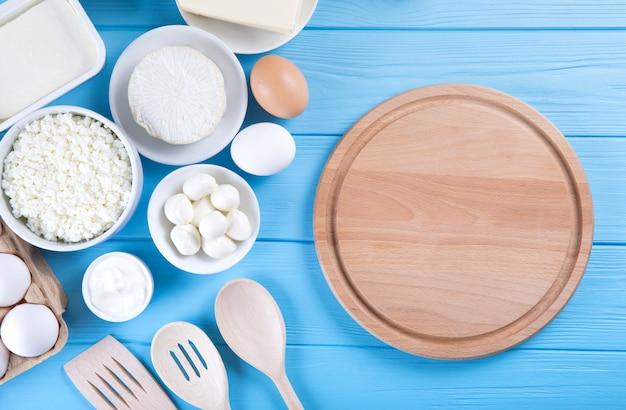 Zuivelproducten op blauwe houten tafel. zure room, melk, kaas, ei en boter.