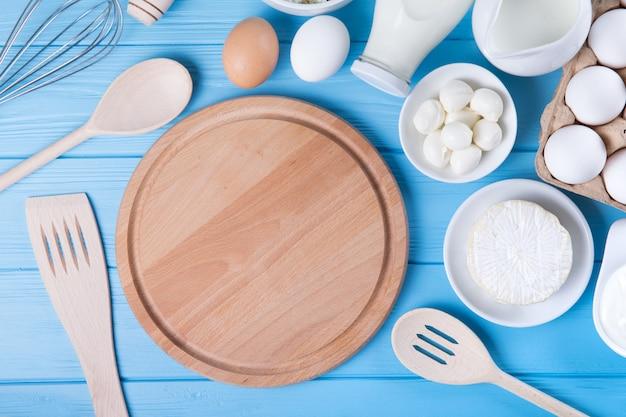 Zuivelproducten op blauwe houten tafel. zure room, melk, kaas, ei en boterachtergrond