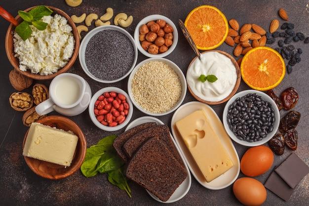 Zuivelproducten, peulvruchten, eieren, noten, chocolade, papaver, sesam, chocolade. donkere achtergrond, bovenaanzicht