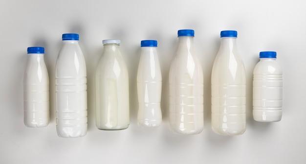 Zuivelproducten verpakking, flessen en glazen met melk geïsoleerd op wit