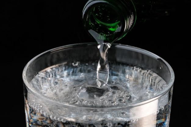 Zuiver koolzuurhoudend water gieten uit een fles in een transparant glas op een zwarte muur close-up macro