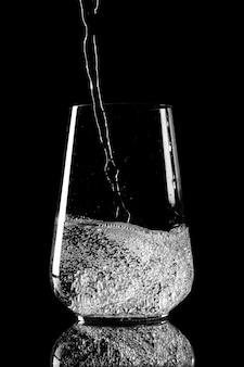 Zuiver water gieten in een glazen beker op een zwarte achtergrond