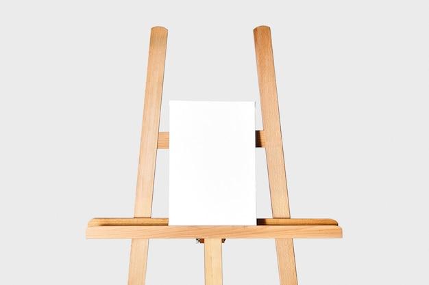 Zuiver wit synthetisch canvas gespannen op een houten brancard staand op een houten schildersezel voor kunstenaars.