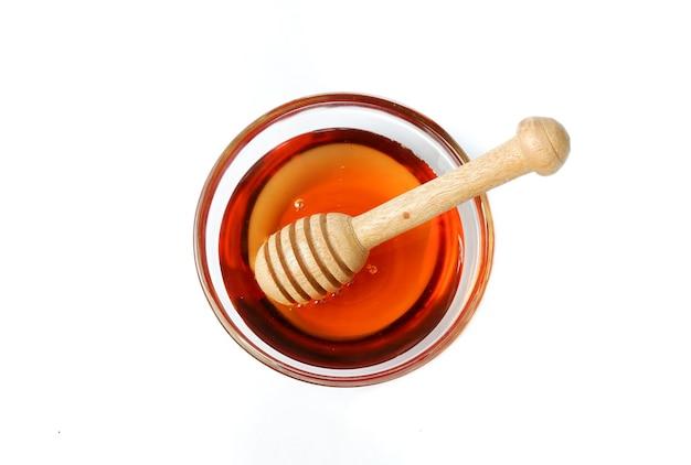 Zuivere honing glazen kom met honing houten lepel geïsoleerd op een witte achtergrond