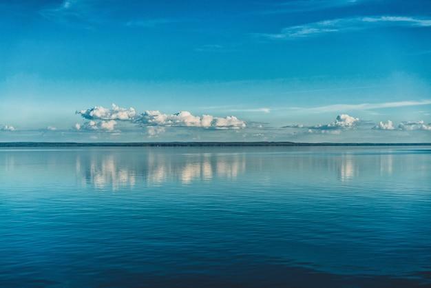 Zuivere witte wolken aan de hemel weerspiegeld in het water van de zee