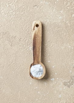 Zuiveringszout in houten lepel op beige kleur tabelachtergrond, bovenaanzicht