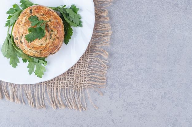 Zure gogal geserveerd op een schaal met peterselie-garnering op marmeren tafel.
